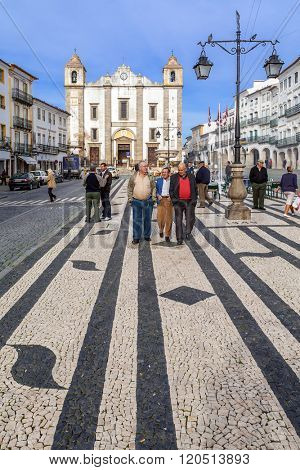 Evora, Portugal - December 1, 2015: Locals strolling in the Giraldo Square with the typical Portuguese cobblestone pavement and the Santo Antao Church in background. UNESCO World Heritage Site.