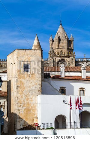 Evora, Portugal - December 1, 2015: The dome of the Evora Cathedral seen behind a medieval tower. Romanesque and Gothic architecture. UNESCO World Heritage Site.