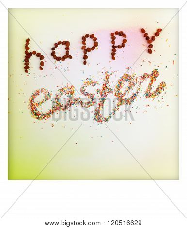 Happy Easter phrase made from raisins and colorful baking sugar over colorful background with copy space and white polaroid frame top view poster