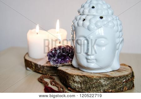 spiritual ritual meditation face of Buddha ametist candles on wooden white background