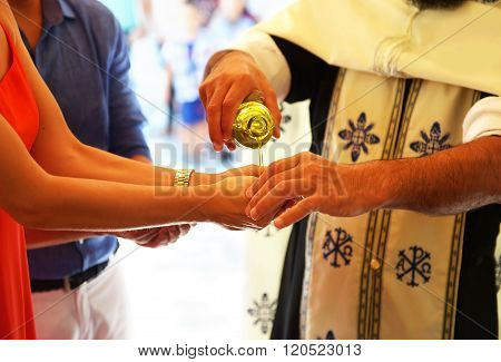 priest puts the baptism oil on the hand of godmother - Orthodox christening
