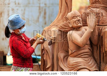 KANCHANABURI, THAILAND, JANUARY 19, 2016 : A Thai woman is sanding a religious Buddhist statue with a drill, for the new Mettadharmabodhiyan temple in Kanchanaburi, Thailand