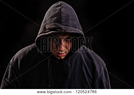 Silhouette of man in the hood or hooligan over dark background