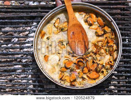 Mussels simmer in a creamy sauce over an open fire.
