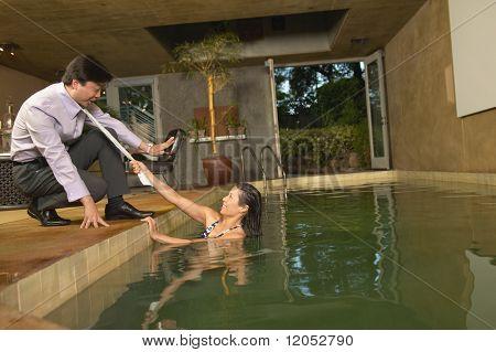 Woman pulling man into swimming pool