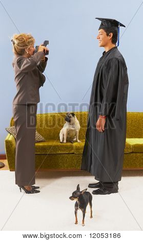 Mother photographing graduate son