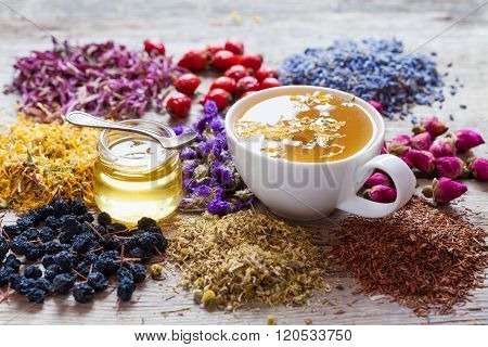 Cup Of Tea, Honey, Healing Herbs, Herbal Tea Assortment And Berries On Table.