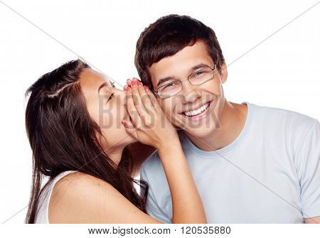 Pretty girl whispering secret in ear of her laughing friend isolated on white background - conversation concept