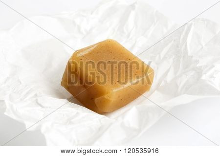 Single Luxury Unwrapped Caramel Toffee On White Wrapper In Perspective.