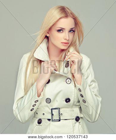 Beautiful model blonde in a gray cloak .