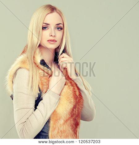 Beautiful model blonde in a trendy fur vest