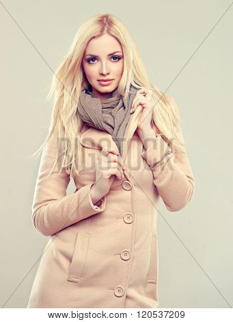 Beautiful model blonde in a beige coat with a warm scarf