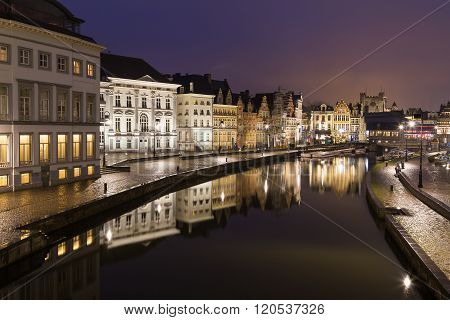 A view of beautiful old buildings along Korenlei and the River Leie in Ghent Old Town at night. Reflections can be seen in the water.
