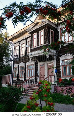 Tomsk/Russia - august 2015: Beautiful wooden carved houses framed ripe rowan in Tomsk, Russia.
