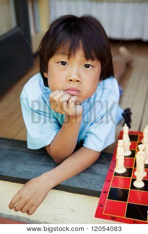 Young boy on stairs with chess set