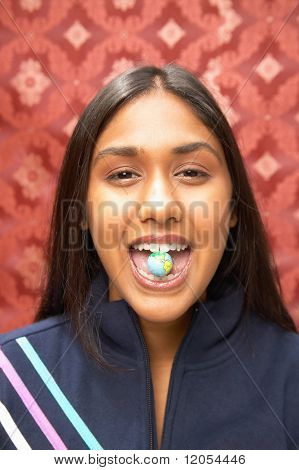Portrait of teenage girl with candy between teeth