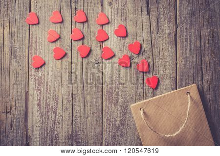Paper gift bag with red hearts on wooden table