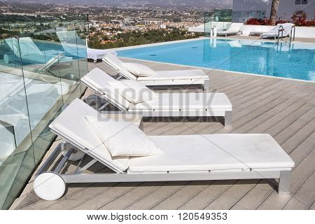 Swimming Pool Area With  White Sun Beds At The Modern Resort.