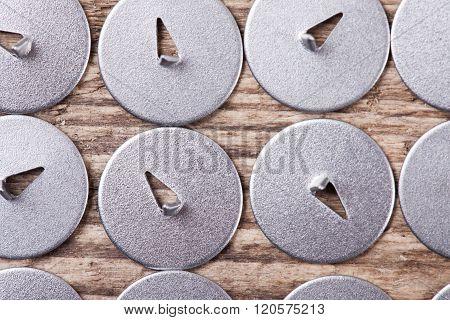 set of metal drawing pins top view macro background