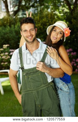 Young couple having fun in the garden, woman sticking tongue, smiling happy.