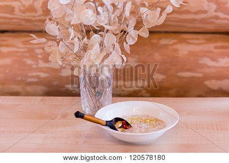 Porridge With Butter And A Wooden Spoon Out Of Focus In A Wooden House