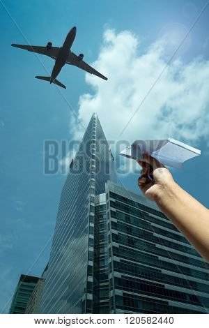 a woman's hand play with a paper airplane