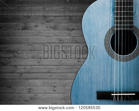 Part of a blue acoustic guitar on a gray wooden background.