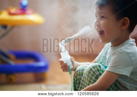 Little boy makes inhalation at home, taking medication to bronchial tubes. Exhales steam through the