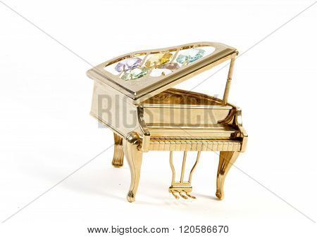 miniature golden piano with gemstones isolated on white background