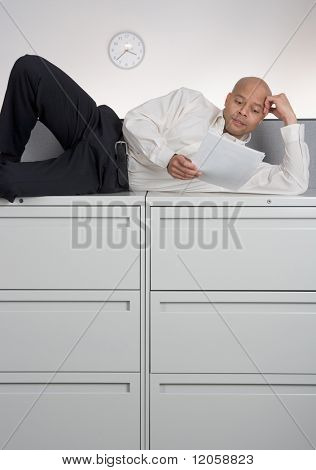 Businessman laying on filing cabinet
