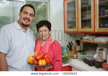 Middle aged woman holding a plate of peppers