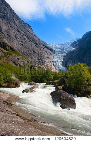 Norway. Summer day at a glacier Briksdal. A stream of thawed snow against mountains and a glacier