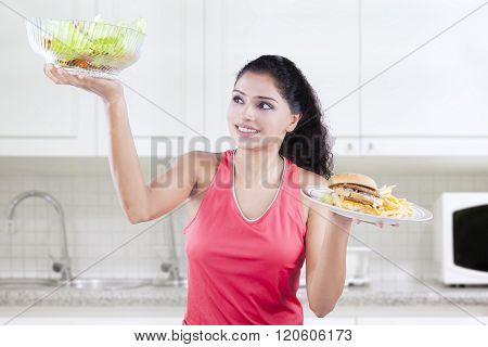 Female Model Compares Hamburger And Salad