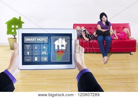 Picture of smart house controller applications on the digital tablet screen. Shot with young mother sitting on sofa with her children at home