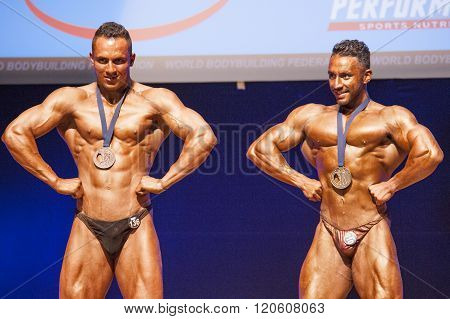 Male Bodybuilders Celebrate Their Championship Victory On Stage