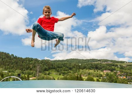 Young Boy Jumping On Bouncing Pillow