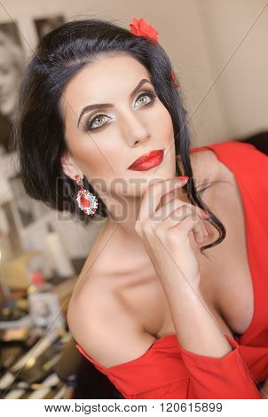 Beautiful young woman with creative make-up and hair style posing. Fashionable attractive brunette