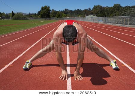 Male track runner stretching