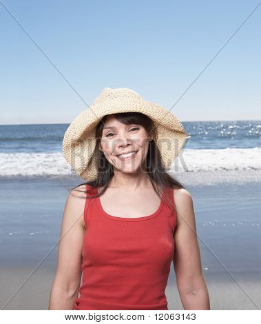 Portrait of woman standing at beach wearing straw hat