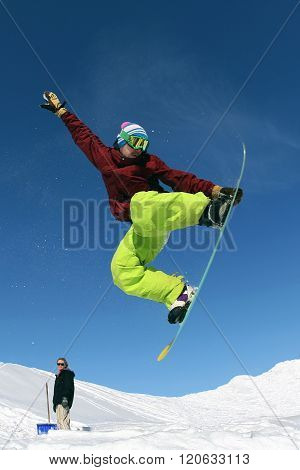 Jumping snowboarder keeps one hand on snowboard in mountains in ski resort on blue sky background