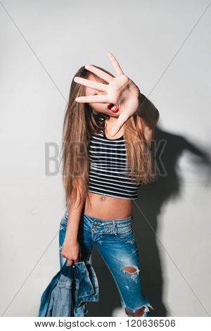 Girl on white background shows sign stop