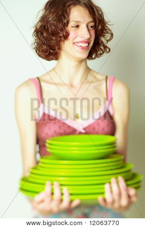 Woman holding stack of dishes