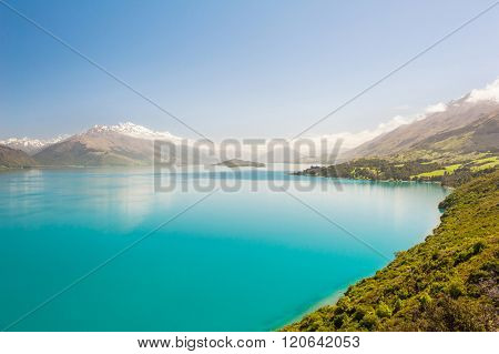 Beautiful blue lake Wakatipu with mighty Southern Alps mountains on horizon. Otago region, New Zealand.