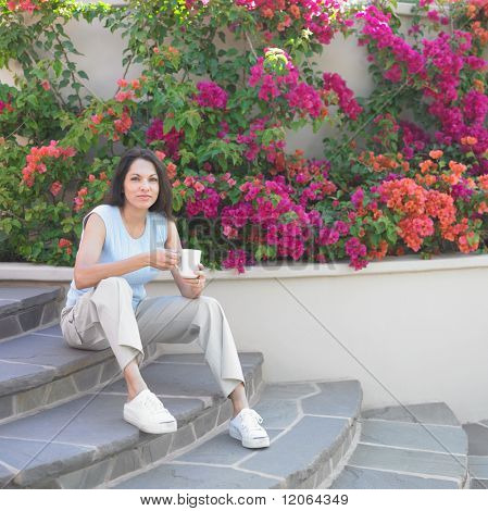 Woman sitting on steps with coffee