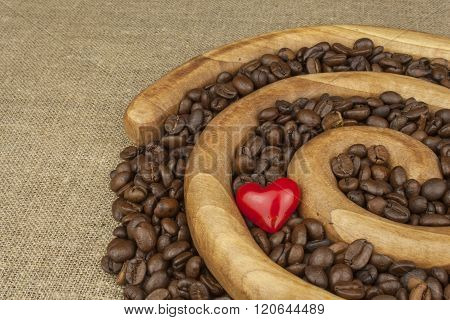 We love fresh roasted coffee. Roasted coffee beans in a wooden spiral on the canvas background