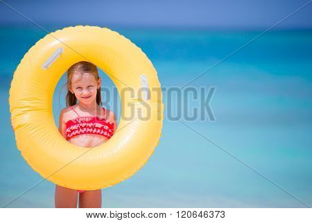 Adorable little girl with inflatable rubber circle during beach vacation