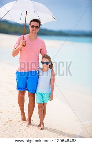 Father and kid at beach with umbrella hiding from sun