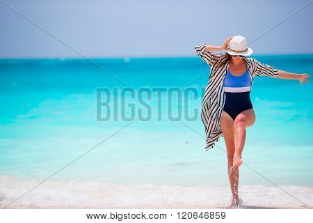 Young happy woman in swimsuit on white beach