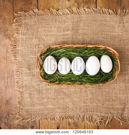 White Easter eggs in grass in brown basket