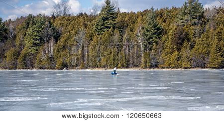 A frozen bay on Lake Champlain with lone ice fisherman